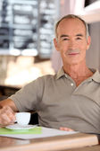 Senior man drinking a cup of expresso — Stock Photo