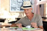 Senior gentleman enjoying free time in cafe — Stock Photo