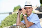Senior gentleman admiring view with binoculars — Stock Photo