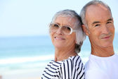 Elderly couple at the beach together — Stock Photo