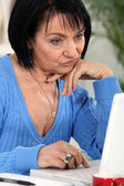 Annoyed woman looking at her laptop — Stock Photo