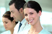 Smiling hospital nurse standing with colleagues — Stock Photo