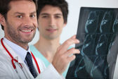 Smiling doctor holding xrays — Stock Photo
