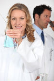 Laboratory technician testing liquid while her colleague makes a phone call — Stock Photo