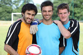 Three football players in casual clothes posing for the photo — Stock Photo