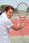 Człowiek przytrzymanie rakieta tenisowa — Zdjęcie stockowe