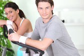 Couple using running machines — Stock Photo