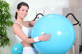Bir spor salonunda egzersiz topu ile gülümseyen kadın — Stok fotoğraf