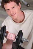 Sporty man lifting barbell — Stock Photo