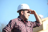 Tradesman shielding his eyes from the sunlight — Stock Photo