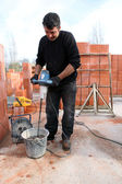 Workman using a cement paddle whisk — Stock Photo
