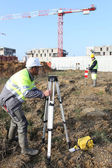 Civil engineers on site with surveying equipment — Stock Photo