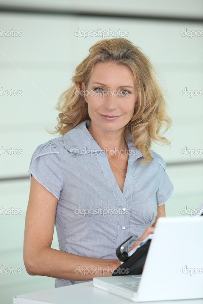Smiling woman putting a date in her diary — Stock Photo #7891031