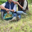 Couple of grape pickers sat on the grass - Stock Photo