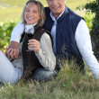 Couple drinking wine in their vineyard - Photo