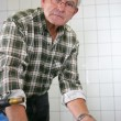 Elderly man gluing parts together - Stock Photo
