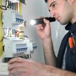Electrician examining fuse box — Stock Photo