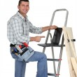 Builder with wood and a laptop - Stock Photo