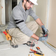 Man snipping wall wiring - Stock Photo