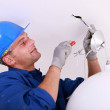 Electrician wiring a ceiling light — Stock Photo