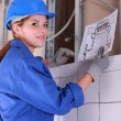 Female electrician looking at a diagram — Foto de Stock
