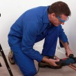 Plumber fixing copper pipe to wall — Stock Photo