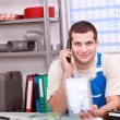 Stock Photo: Mon telephone checking plumbing part