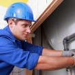 Stock Photo: Young plumber fitting pipes