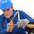 Stock Photo: Laborer sawing copper pipe