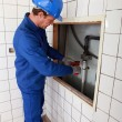 Stock Photo: Plumber working in tiled room
