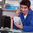 DIY store employee holding part and speaking on telephone — Stock Photo #7904340