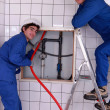Plumbers working in a tiled room — Stock Photo