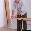 Handyman measuring a wooden board with a measure-tape — Stock Photo