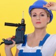Stock Photo: Blonde womwearing overall posing with drill and adjusting her hel