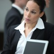 Female executive working with colleague at a laptop — Stock Photo