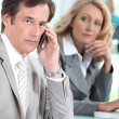 Stock Photo: A businessman using a mobile phone and being observed by a businesswoman du