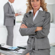 Businesswoman sitting on desk with arms folded — Stock Photo #7905202