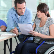 Young woman in wheelchair working with a male colleague — Stock Photo