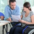 Young woman in wheelchair working with a male colleague — Stock Photo #7905239