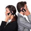 Businessman and businesswoman telephoning — Stock Photo