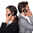 Businessman and businesswoman telephoning - Stock Photo