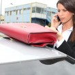 Royalty-Free Stock Photo: Businesswoman on the phone next to her car