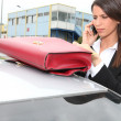 Businesswoman on the phone next to her car - Stock Photo