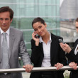 Businessmen and women on the phone outside. — Stock Photo #7905567