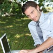 Relaxed businessman on the grass - Stock Photo