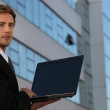 Young businessman using a laptop with a blank screen — Stock Photo
