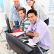 Four smiling gathered round a computer in a classroom — Foto de Stock