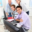 Four smiling gathered round a computer in a classroom — Stockfoto