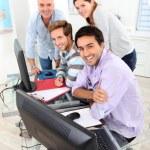 quatre souriant rassemblé autour d'un ordinateur dans une salle de classe — Photo