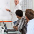 Stock Photo: Young men in classroom with trainer